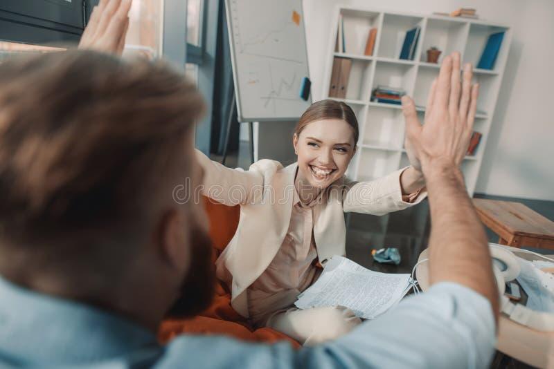 Jeune homme d'affaires et femme d'affaires donnant la double haute cinq dans le bureau photo stock