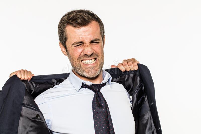 Jeune homme d'affaires fâché ouvrant son costume pour l'étouffement d'entreprise photographie stock