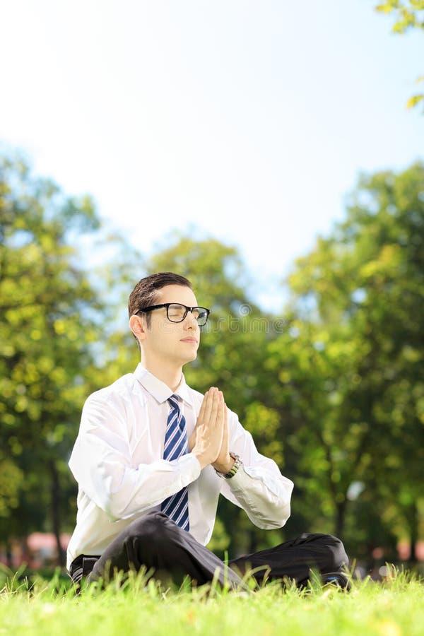 Jeune homme d'affaires faisant l'exercice de yoga posé sur une herbe photo libre de droits