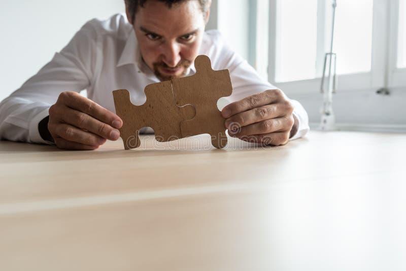Jeune homme d'affaires focalisé joignant deux morceaux assortis de puzzle images stock