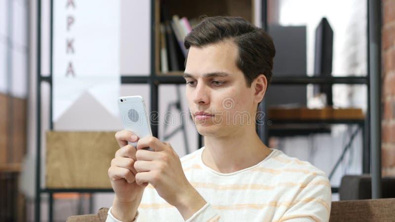 Jeune homme d'affaires gai utilisant le smartphone, le travail et la pause-café photographie stock libre de droits