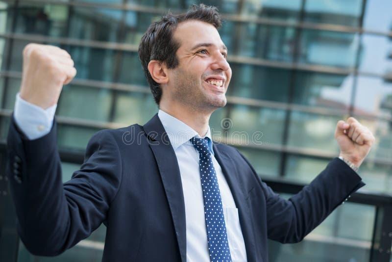 Jeune homme d'affaires heureux célébrant la promotion du travail images libres de droits