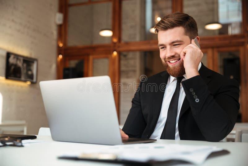 Jeune homme d'affaires heureux dans le costume noir parlant au téléphone portable, l image libre de droits
