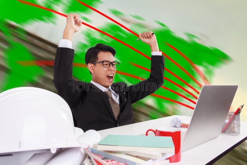 Jeune homme d'affaires heureux de travailler avec succès images stock