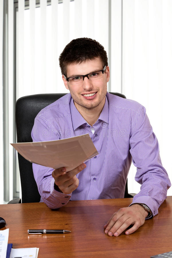 Jeune homme d'affaires heureux donnant des documen images stock