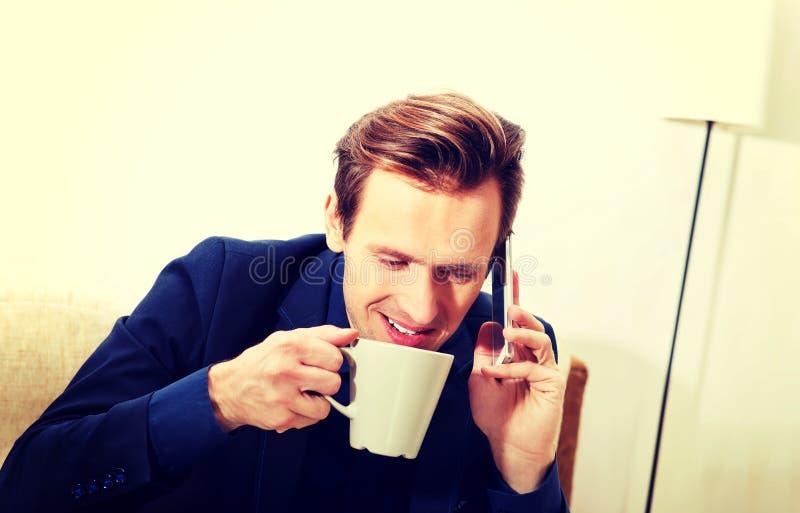 Jeune homme d'affaires heureux parlant par un téléphone et un café ou un thé potable image stock