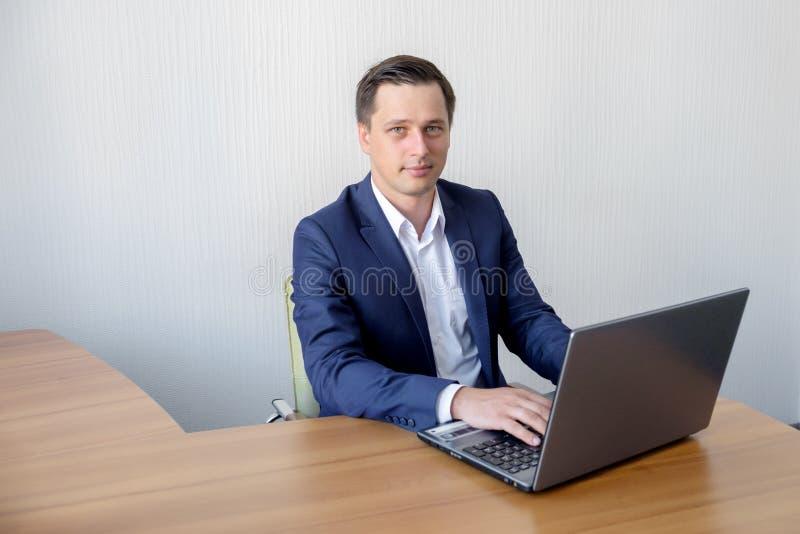 Jeune homme d'affaires heureux utilisant l'ordinateur portable à son bureau photo libre de droits