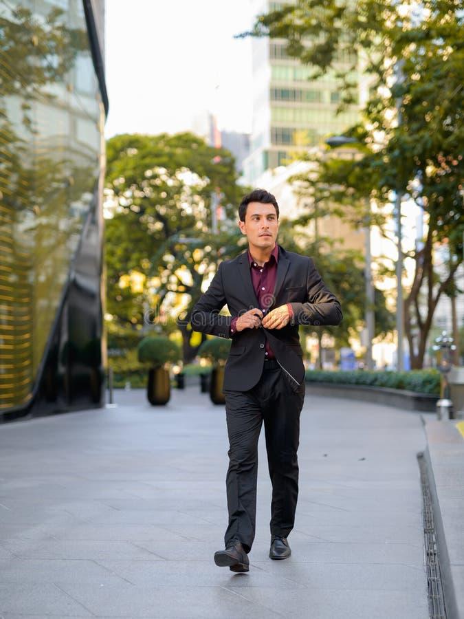 Jeune homme d'affaires hispanique réfléchi marchant en dehors de l'immeuble de bureaux photos libres de droits