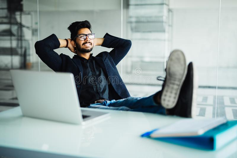 Jeune homme d'affaires indien travaillant dans son bureau avec des pieds sur le bureau images libres de droits