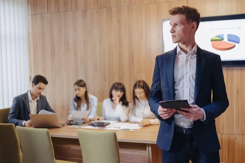Jeune homme d'affaires ?l?gant utilisant une veste et une chemise sur le fond d'un bureau fonctionnant avec des personnes travail photographie stock