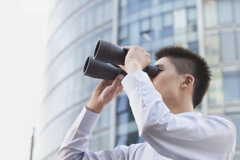 Jeune homme d'affaires Looking Through Binoculars photos stock