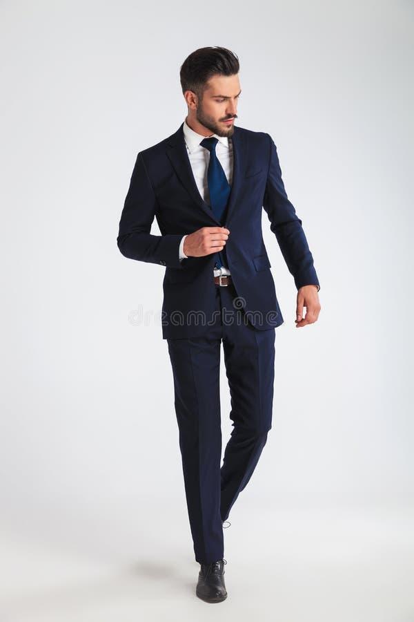 Jeune homme d'affaires marchant et boutonnant son costume de marine images libres de droits