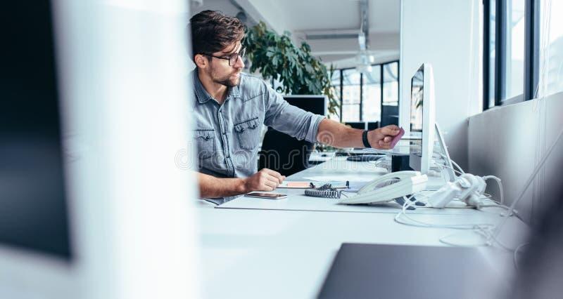 Jeune homme d'affaires mettant la note de post-it sur le moniteur d'ordinateur photographie stock libre de droits