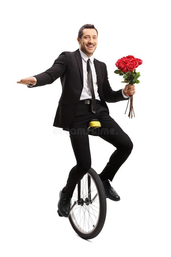 Jeune homme d'affaires montant un monocycle et tenant un bouquet des roses rouges photos libres de droits