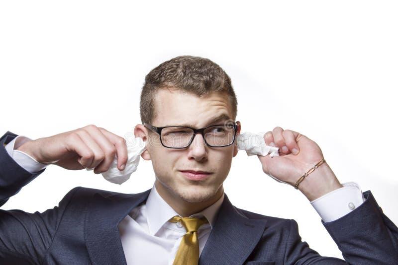 Jeune homme d'affaires nettoyant ses oreilles avec un tissu de coton photo libre de droits