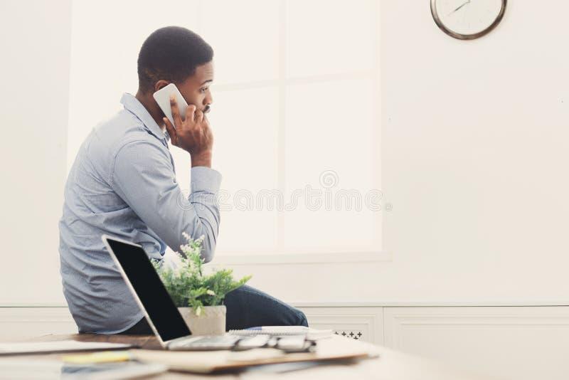 Jeune homme d'affaires noir ayant l'entretien de téléphone image stock