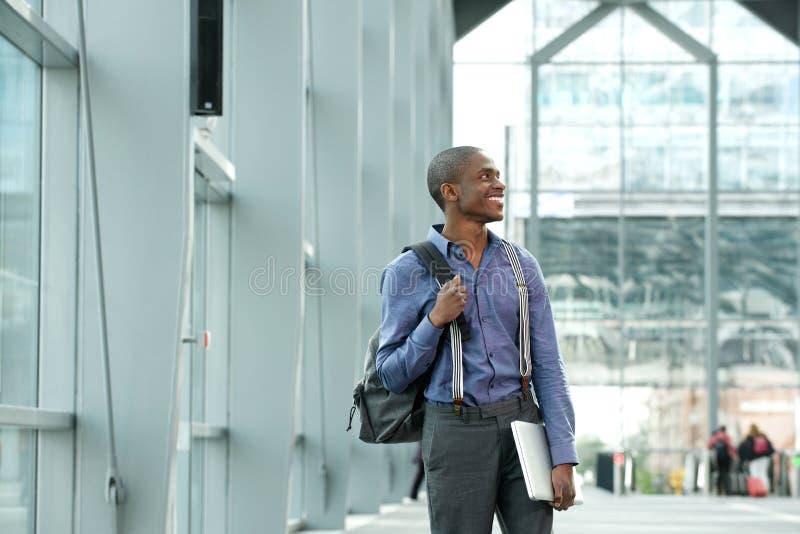 Jeune homme d'affaires noir tenant l'ordinateur portable et le sac dans le bâtiment photo stock