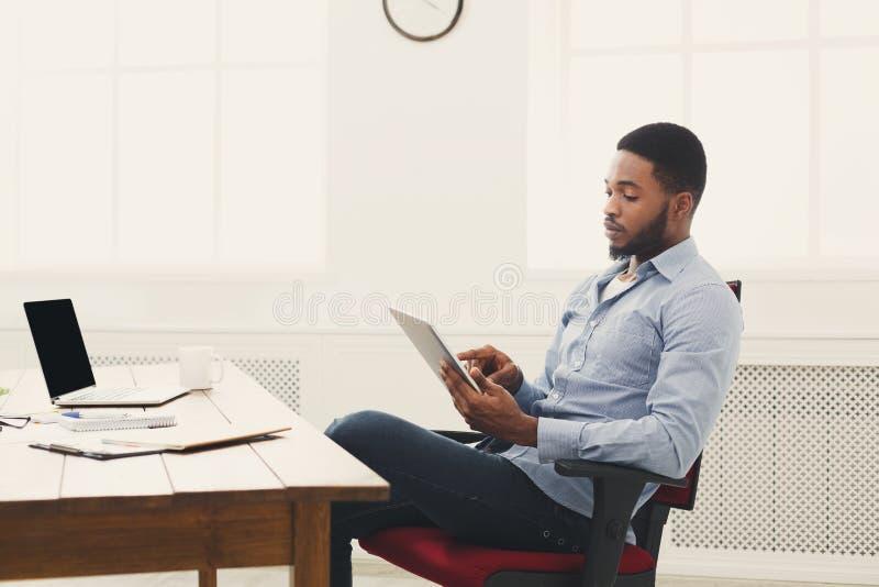 Jeune homme d'affaires noir travaillant avec le comprimé photographie stock libre de droits