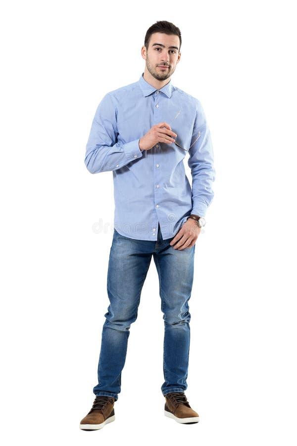 Jeune homme d'affaires occasionnel futé sûr frais tenant des lunettes de soleil regardant l'appareil-photo photo stock