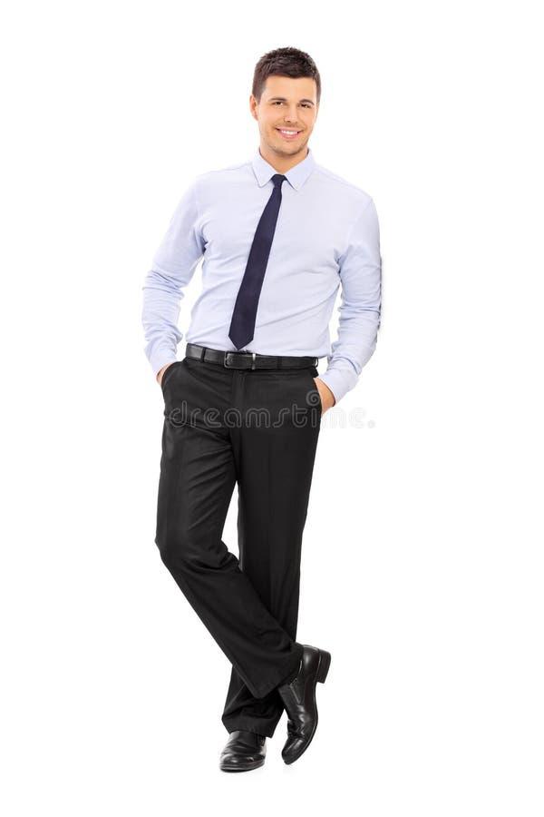 Jeune homme d'affaires occasionnel se penchant contre un mur photo stock