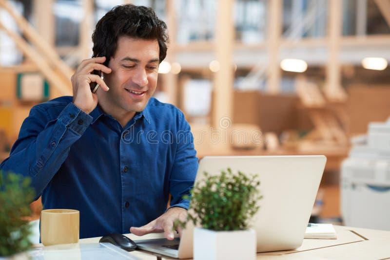 Jeune homme d'affaires occupé dur au travail dans un bureau moderne image libre de droits
