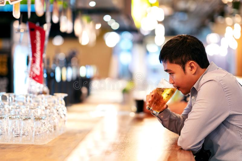 Jeune homme d'affaires ou indépendant asiatique s'asseyant au sentiment potable de bière de barre de boîte de nuit réfléchi Alcoo images libres de droits