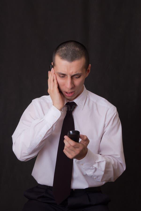 Jeune homme d'affaires parlant à deux téléphones image stock