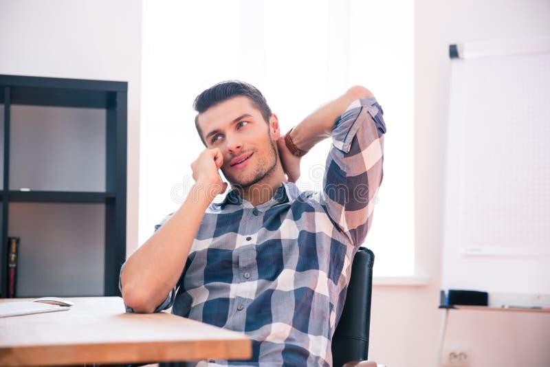 Jeune homme d'affaires parlant du téléphone dans le bureau photos stock