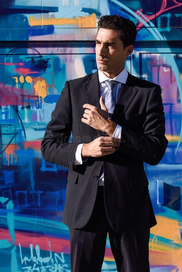 Jeune homme d'affaires portant le costume et la cravatte bleus à l'arrière-plan urbain photographie stock