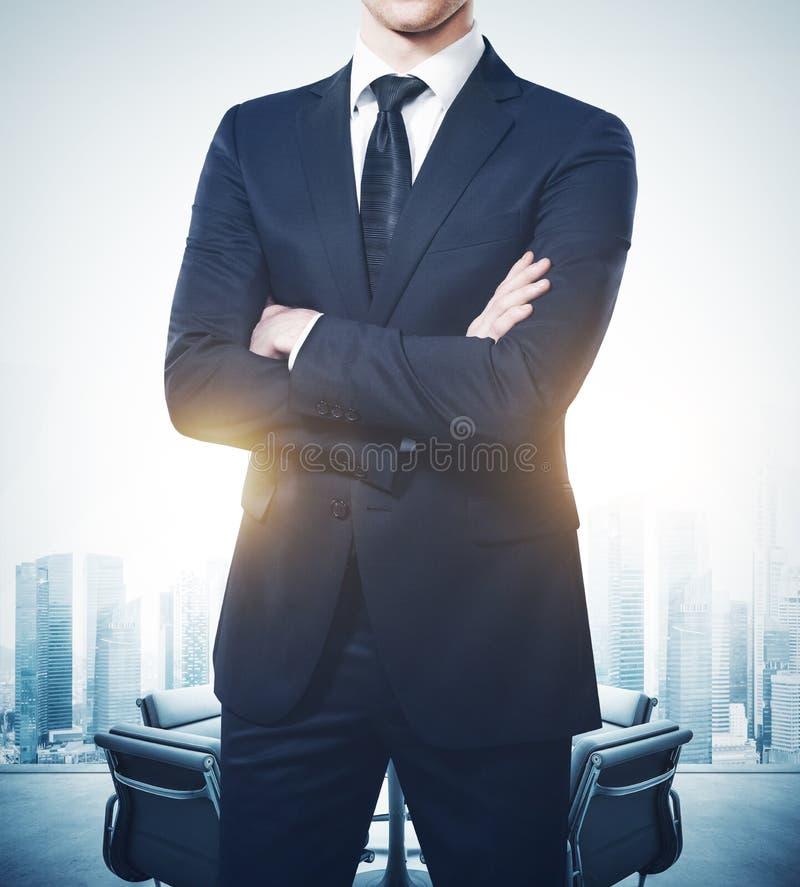 Jeune homme d'affaires portant le costume et les supports modernes dans le lieu de réunion vide photos stock