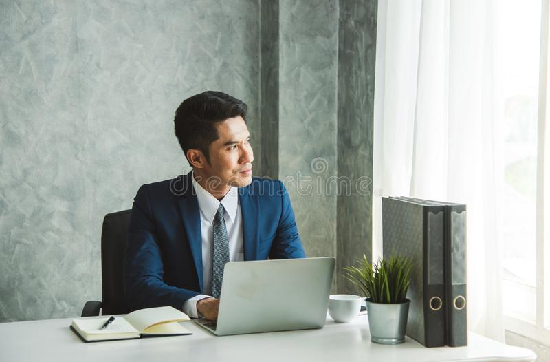 Jeune homme d'affaires Portrait de travail s'asseyant à son bureau dans le bureau photo libre de droits