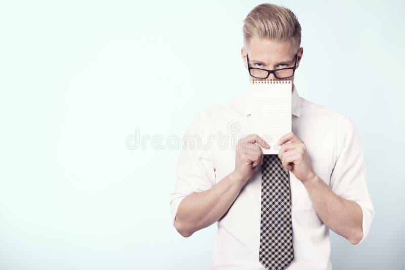 Jeune homme d'affaires présent le bloc - notes blanc. images libres de droits
