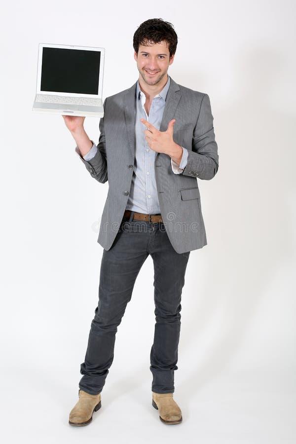 Jeune homme d'affaires présent le nouvel ordinateur portable images libres de droits