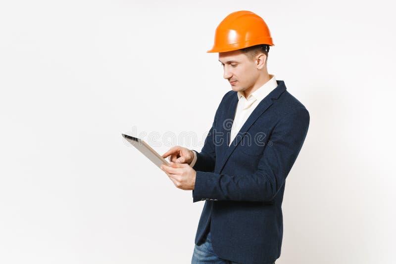Jeune homme d'affaires réussi bel dans le costume foncé, casque orange de construction protectrice utilisant l'ordinateur de PC d photos stock