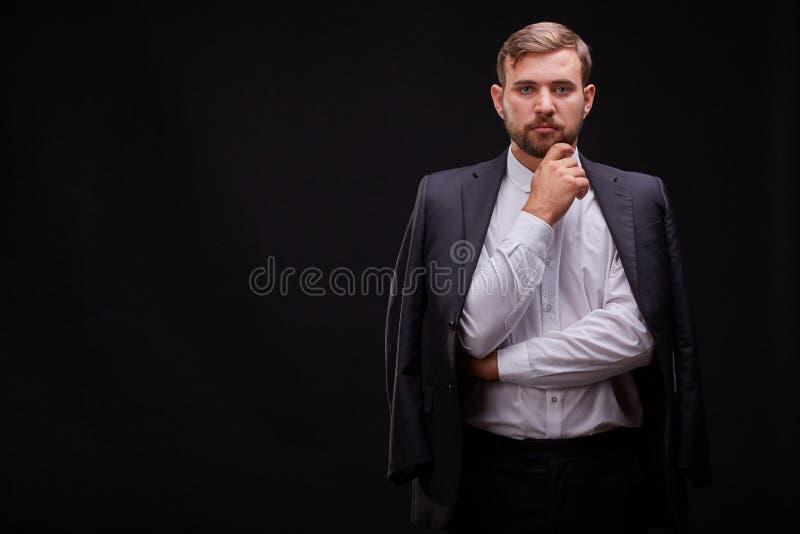 Jeune homme d'affaires réussi dans un costume noir posant sur un fond noir Concept d'affaires photographie stock