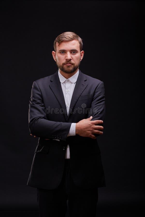 Jeune homme d'affaires réussi dans un costume noir posant sur un fond noir Concept d'affaires images libres de droits