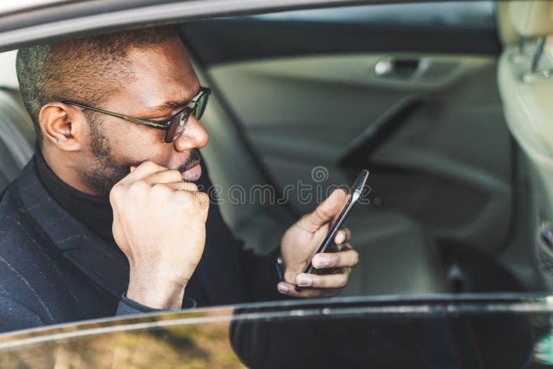 Jeune homme d'affaires r?ussi parlant au t?l?phone se reposant dans la banquette arri?re d'une voiture ch?re N?gociations et affa photographie stock libre de droits