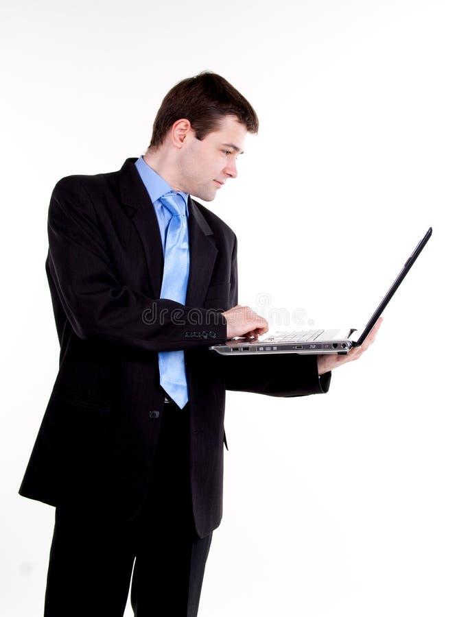 Jeune homme d'affaires restant avec l'ordinateur portatif photo stock