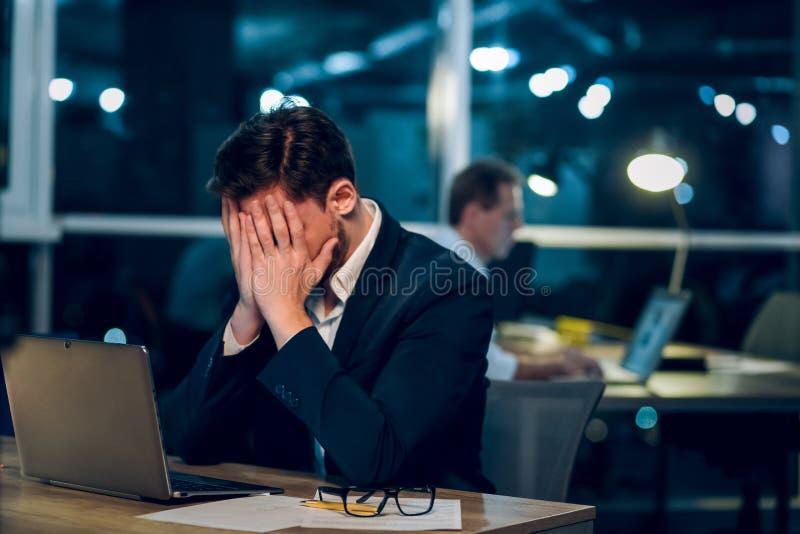 Jeune homme d'affaires restant le travail en retard images stock