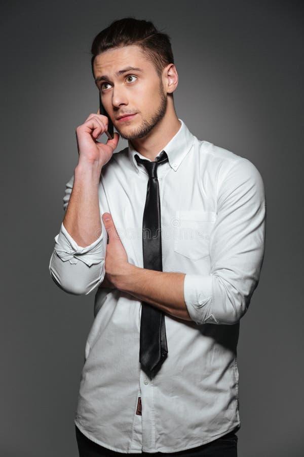 Jeune homme d'affaires sérieux se tenant et parlant au téléphone portable photo stock