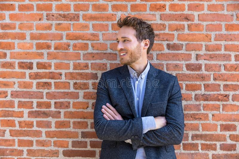 Jeune homme d'affaires d'affaires d'homme sûr d'entrepreneur regardant au portrait latéral sur le fond de mur de briques de burea image libre de droits