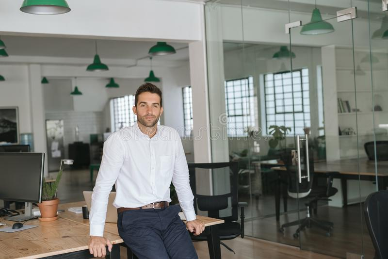 Jeune homme d'affaires sûr se penchant contre un bureau photos libres de droits
