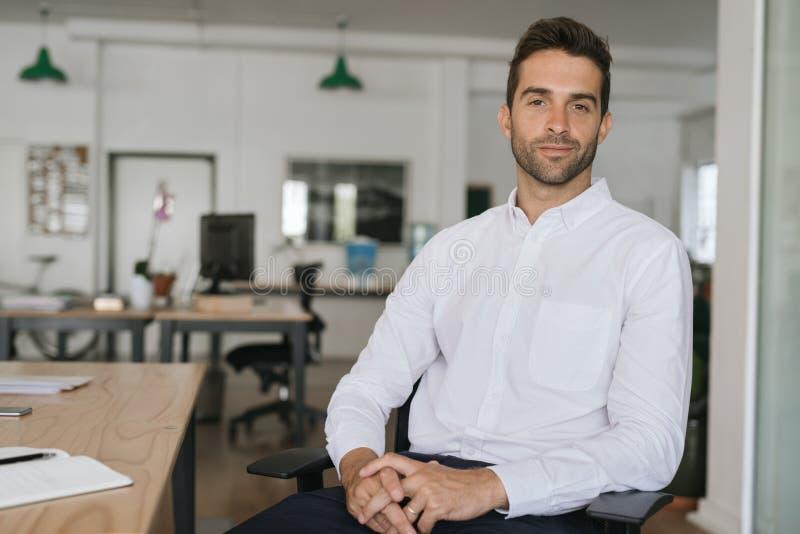 Jeune homme d'affaires sûr seul s'asseyant dans un grand bureau moderne image stock
