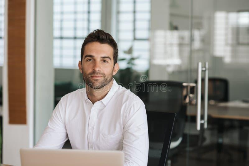 Jeune homme d'affaires sûr travaillant à son bureau image stock