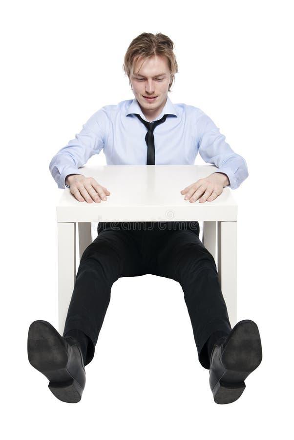 Jeune homme d'affaires s'asseyant au bureau drôle images stock