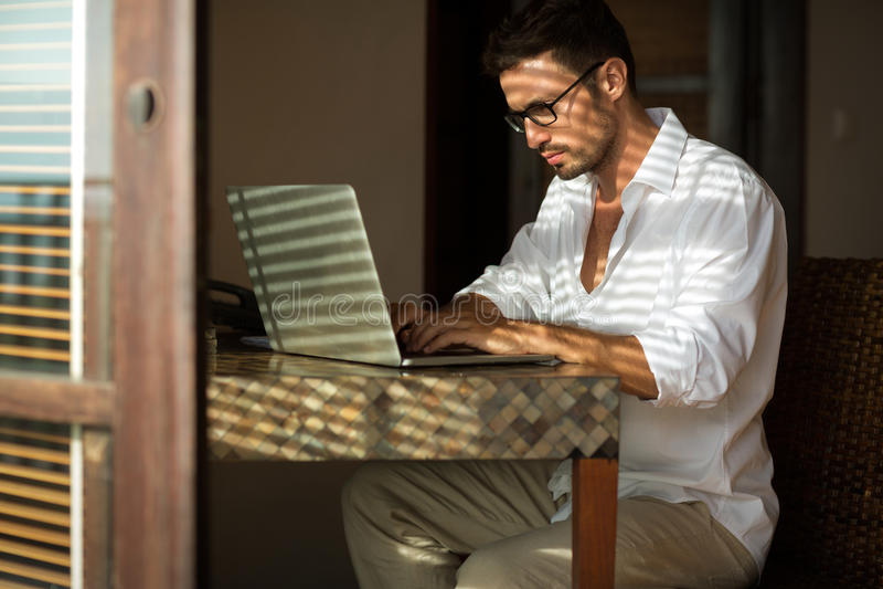 Jeune homme d'affaires s'asseyant au bureau, utilisant l'ordinateur portable photo stock