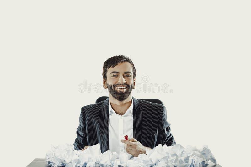 Jeune homme d'affaires s'asseyant avec les feuilles écrasées photo stock