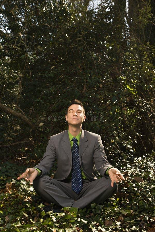 Jeune homme d'affaires s'asseyant dans la méditation photos libres de droits