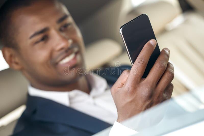 Jeune homme d'affaires s'asseyant dans la voiture jouant le jeu sur le fond brouillé en gros plan joyeux de smartphone images stock
