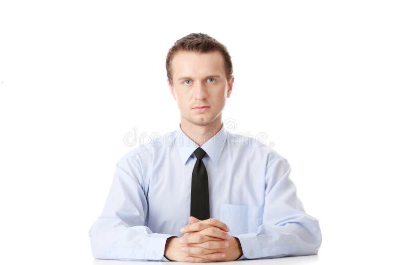 Jeune homme d'affaires s'asseyant derrière le bureau photographie stock libre de droits
